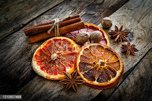 Scented spices: dried orange slices, cinnamon, star anise and nutmeg shot on rustic wooden table. Predominant colors are orange and brown. High resolution 42Mp studio digital capture taken with SONY A7rII and Zeiss Batis 40mm F2.0 CF lens