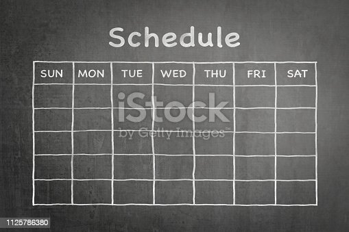 istock Schedule with grid timetable on black chalkboard 1125786380