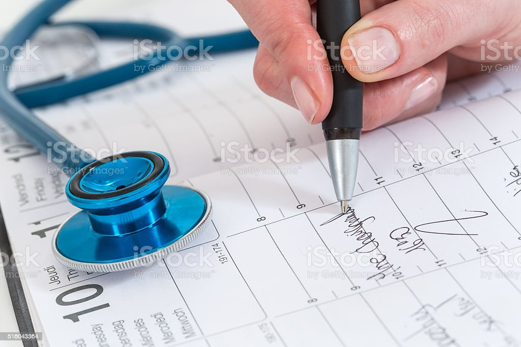 scheduled doctors appointment is wrote on  calendar for  patient stock photo