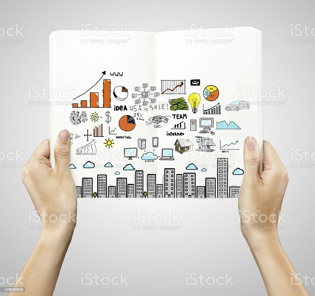 scheme and open book hands holding book with drawing colorized city Book Stock Photo