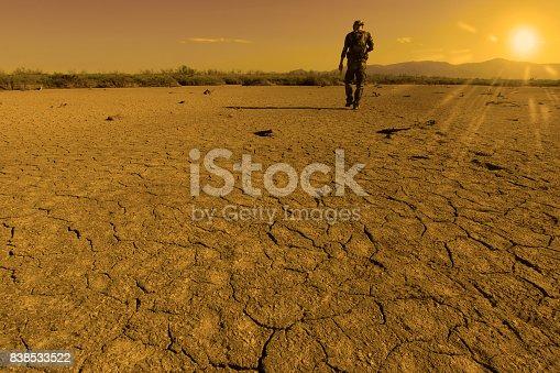 un homme, vu de dos,  se déplace à pied sur un sol aride ; à l'horizon, à droite de l'image brille un soleil ardent. Image métaphore de chaleur, sécheresse, catastrophe climatique.