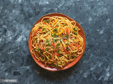 Schezwan Noodles with vegetables in a plate on a wooden table. Top view. Hakka Noodles is a popular Indo-Chinese recipes.