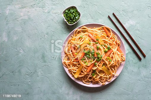 Schezwan Noodles with vegetables in a plate on a green table. Top view. Hakka Noodles is a popular Indo-Chinese recipes.