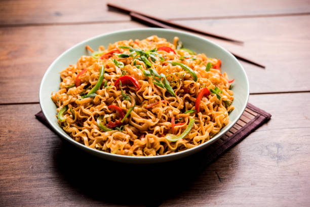 schezwan veg noodles is a spicy and tasty stir fried flat hakka noodles with sauce and veggies. served with chopsticks. selective focus - macarrão imagens e fotografias de stock