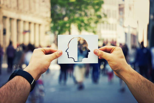 Schizophrenia psychiatric disease Man hands holding a white paper sheet with two faced head over a crowded street background. Split personality, bipolar mental health disorder concept. Schizophrenia psychiatric disease. sensory perception stock pictures, royalty-free photos & images