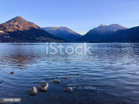 Lake with water birds surrounded by mountains at sunset