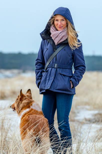 schöne frau macht mit ihrem hund einen spaziergang bin strang - mützenschal stock-fotos und bilder