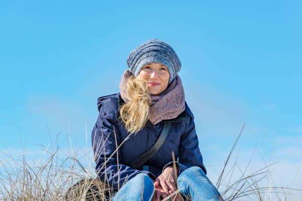 schöne frau sitzt in der sonne auf einer düne - winterjacke lang damen stock-fotos und bilder