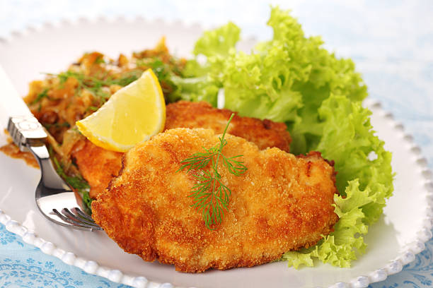 Schnitzel on white plate with salad and lemon. stock photo