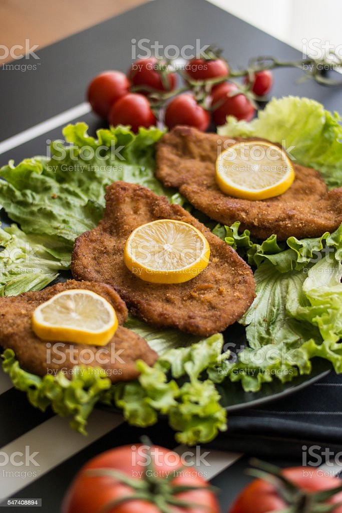 Schnitzel serve with greens and lemon stock photo