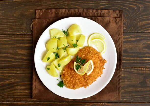 schnitzel mit gekochten kartoffeln - schnitzel braten stock-fotos und bilder