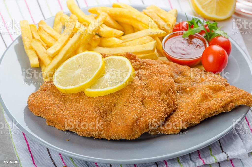 Schnitzel with french fries and a spicy dip stock photo