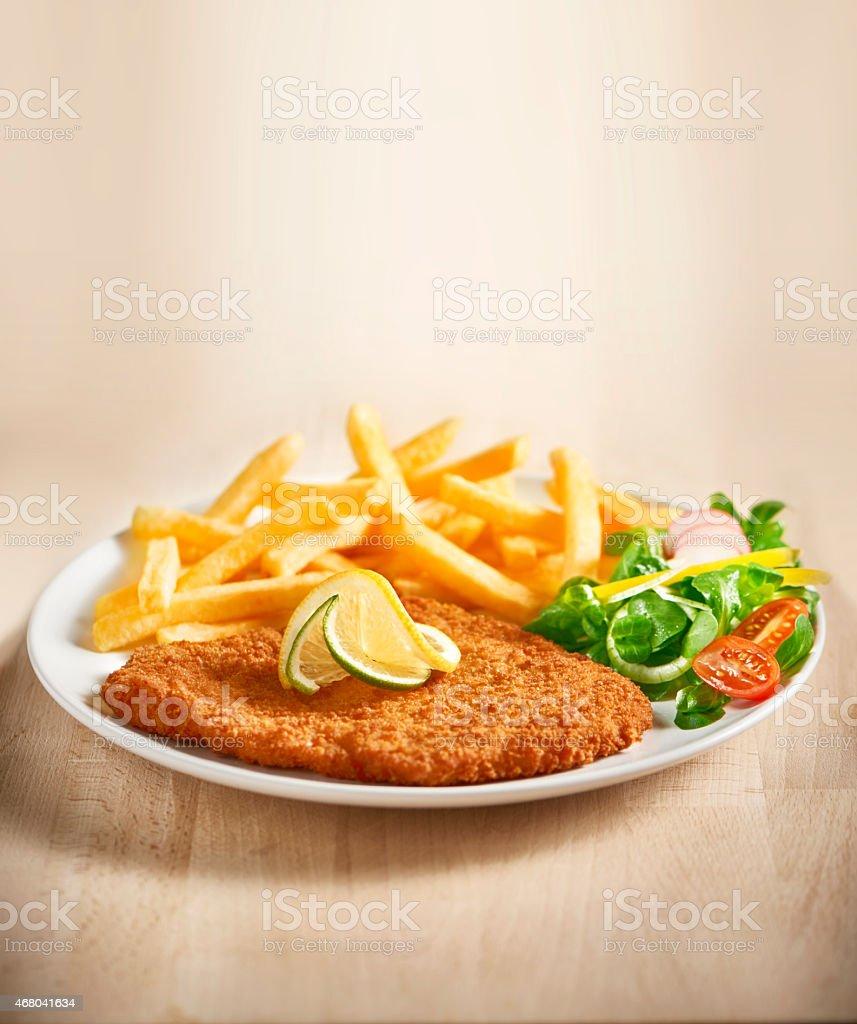 schnitzel with fries stock photo