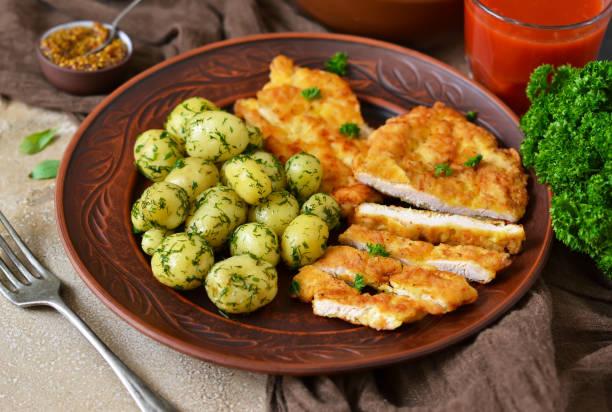 schnitzel mit kartoffeln und salat für das mittagessen auf einem konkreten hintergrund - kürbisschnitzel stock-fotos und bilder