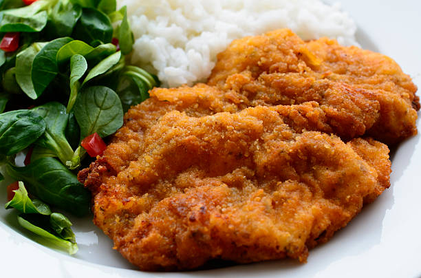 Schnitzel with salad and rice, detail Portion of breaded meat, rice and salad fritter stock pictures, royalty-free photos & images