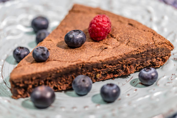 schokoladen tarte mit himbeere und blaubeeren auf einem hellblauen teller - tarte und törtchen stock-fotos und bilder