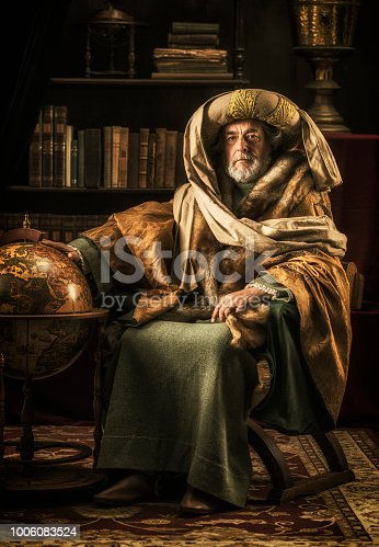 Scholar sitting in his library with old world sphere