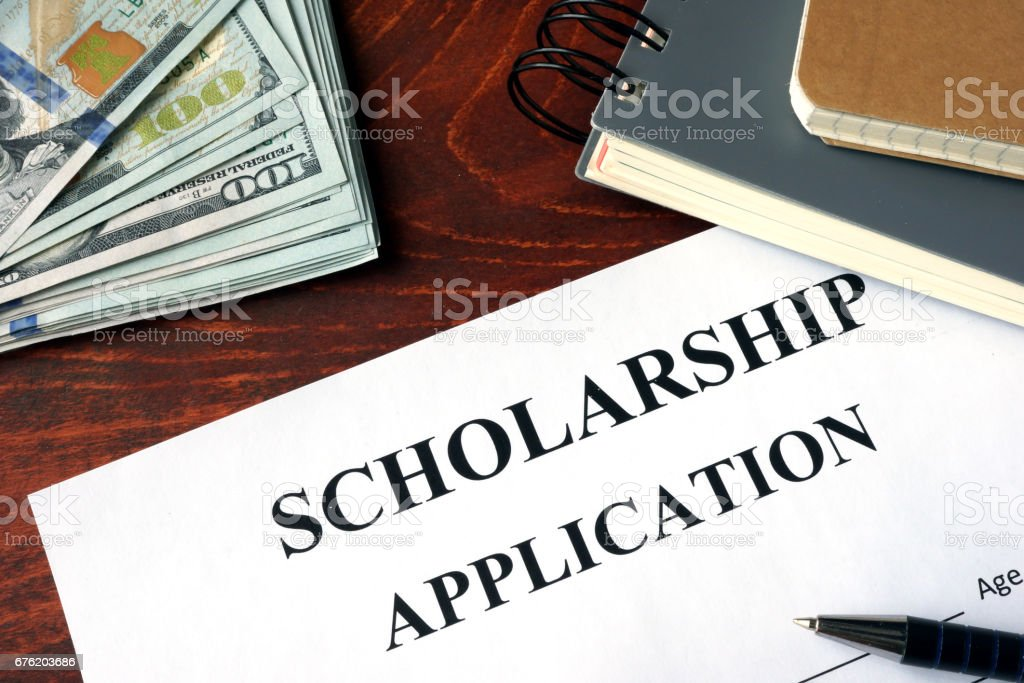 Scholarship Application on a table and dollars. stock photo
