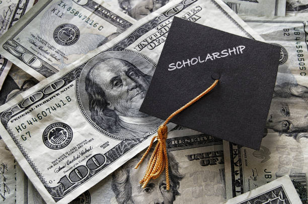 Scholarship graduation cap on cash stock photo