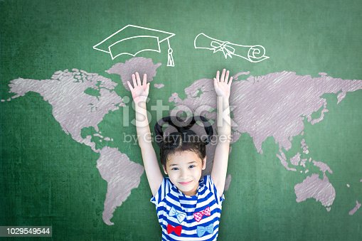 istock Scholarship opportunity and education success concept with school kid with doodle drawing of graduation cap on green chalkboard 1029549544