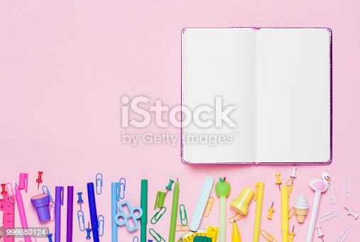 istock School accessories are laid out in the form of a rainbow and emty notrbook. 996680124