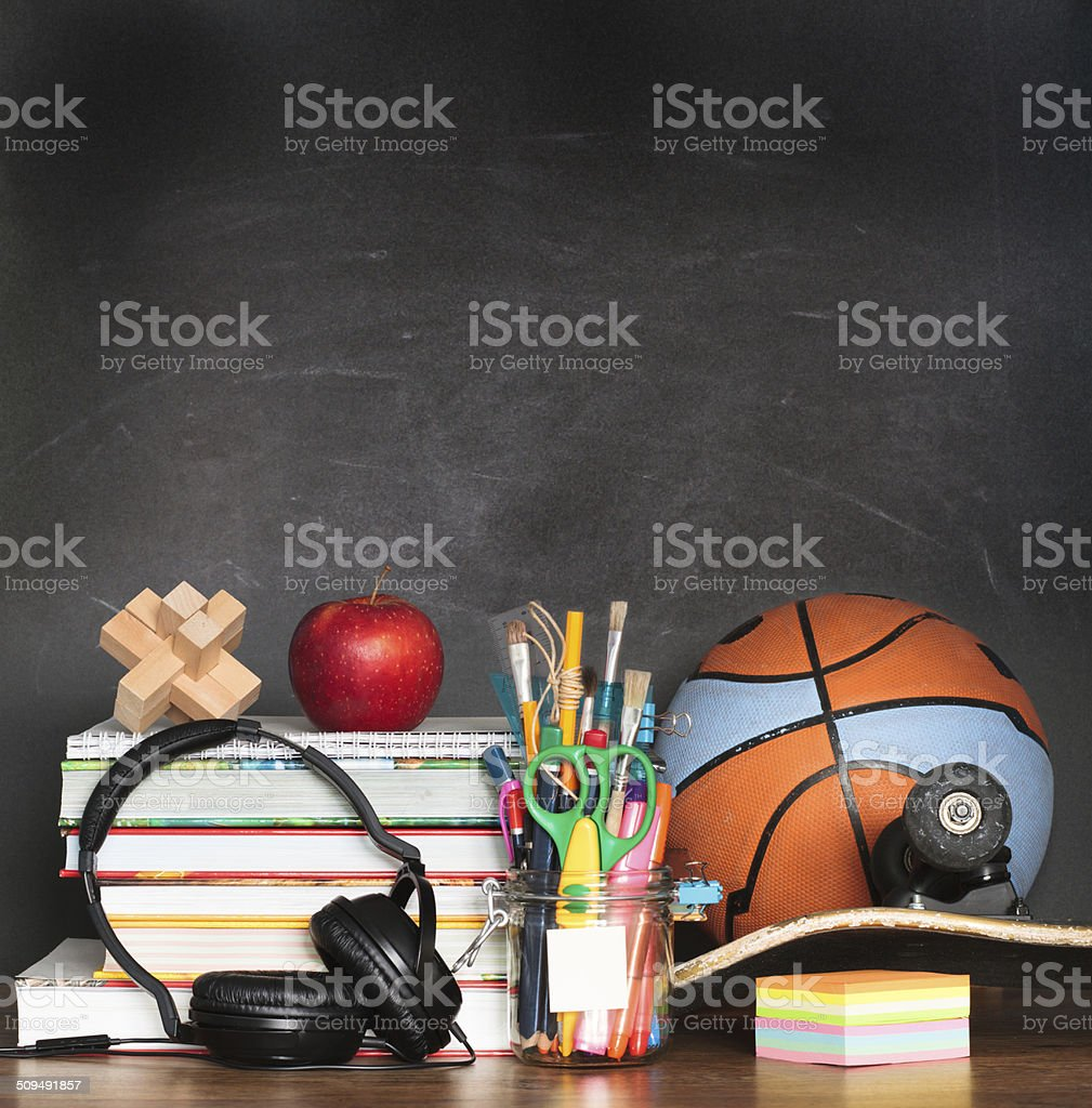 School accessories on desktop with blank blackboard in the backg stock photo