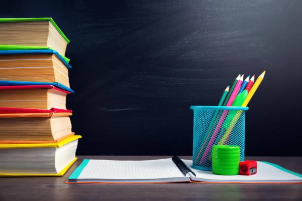 schule-zubehör auf dem tisch mit blackboard-hintergrund - kreide farbe schreibtisch stock-fotos und bilder