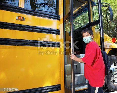 Young elementary school boy climbs on to school bus wearing surgical mask