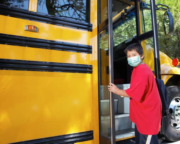 school age boy wearing surgical mask Young elementary school boy climbs on to school bus wearing surgical mask school buses stock pictures, royalty-free photos & images