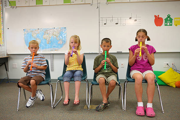 school age children playing colorful recorders in classroom - recorder stock photos and pictures