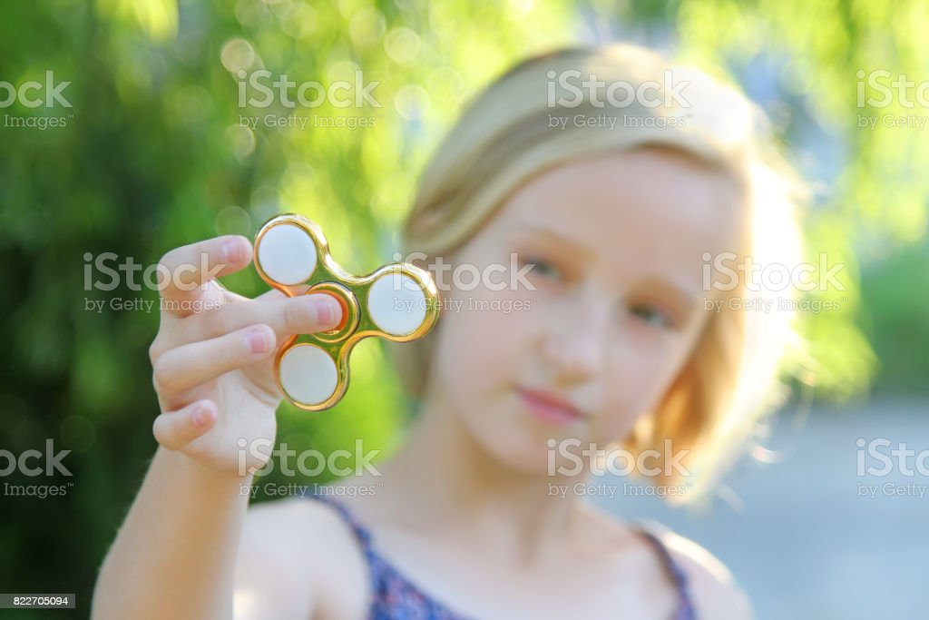 School aged girl playing with a gold fidget spinner. A popular trendy toy. stock photo