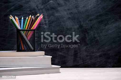 istock School and office supplies and apple in front of blackboard. 666229764