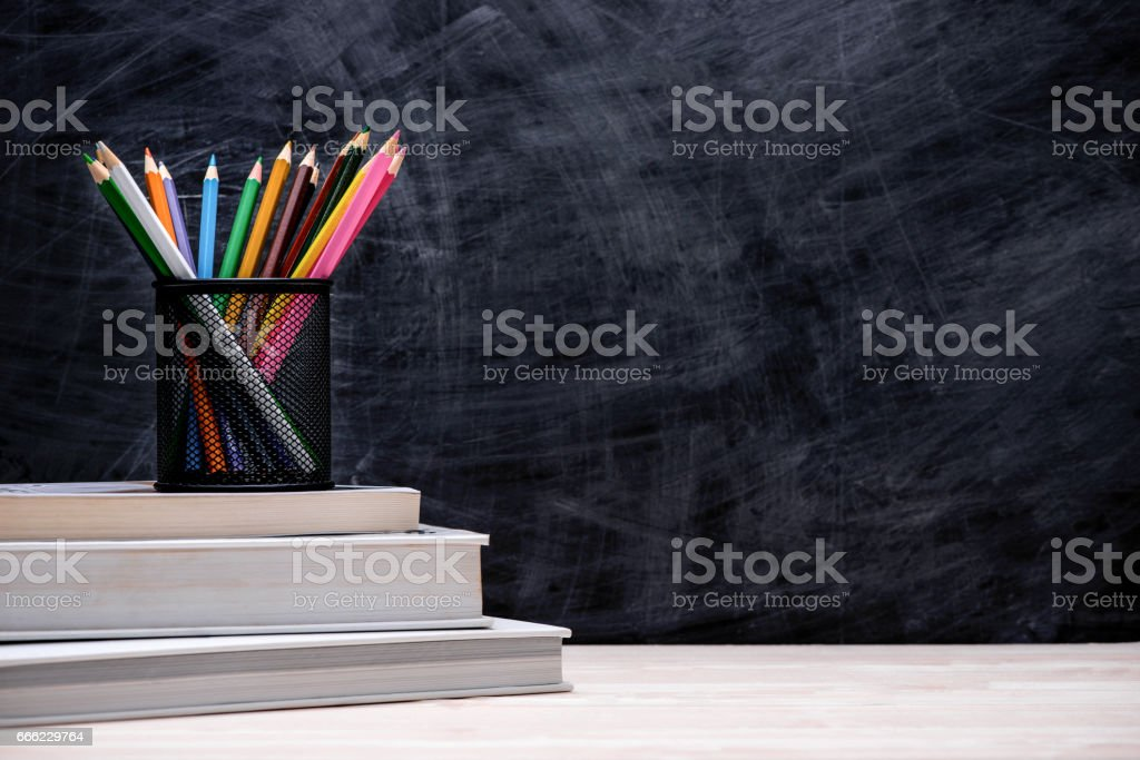 School and office supplies and apple in front of blackboard. stock photo