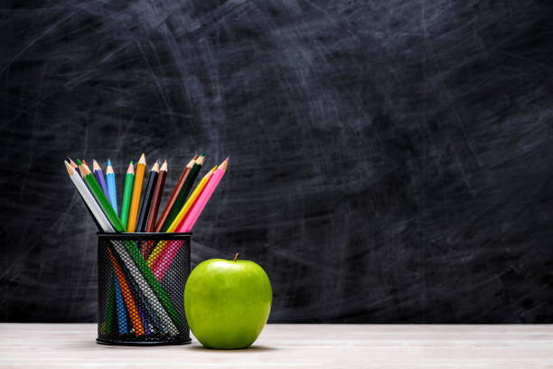 schul- und büromaterial und apple vor tafel. - kreide farbe schreibtisch stock-fotos und bilder