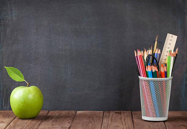 schule und büromaterialien und apple - kreide farbe schreibtisch stock-fotos und bilder