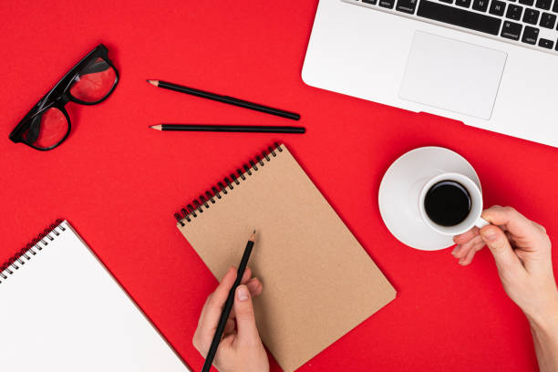 School and office supplies lie neatly on a red background stock photo