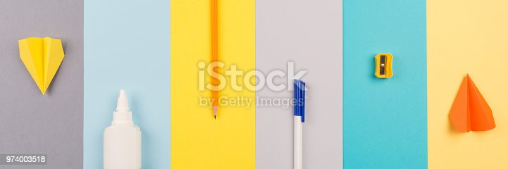 istock school and office supplies on bright striped background. minimum set in yellow, blue, grey and orange color: pen, pencil, sharpener, glue. concept: back to school, minimalism. Flat lay, top view, long banner 974003518