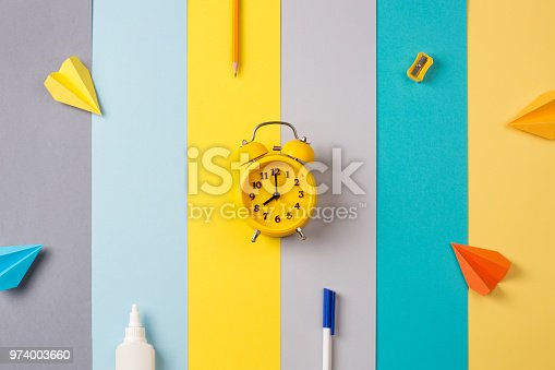 istock school and office supplies on bright striped background. minimum set in yellow, blue, gray and orange color: pen, pencil, sharpener, glue, alarm. concept: back to school, minimalism. Flat lay, top view 974003660