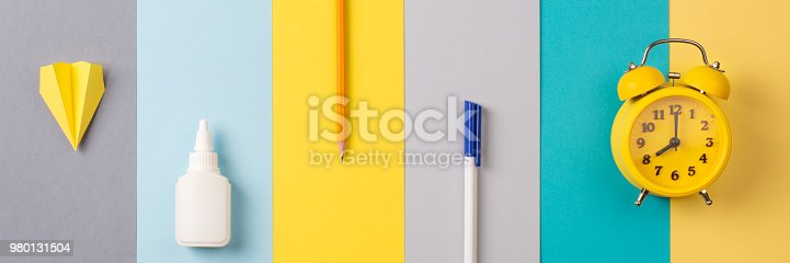 istock school and office supplies on bright striped background. minimum set in yellow, blue, gray color: pen, pencil, glue, alarm. concept: back to school, minimalism. Flat lay, top view, long banner 980131504