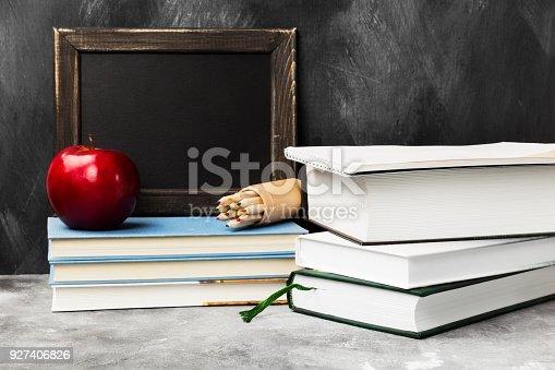 istock School attributes - black board, books, colored pencils, notebook, apple on dark background. Copy space 927406826