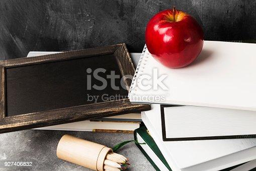 istock School attributes - black board, books, colored pencils, notebook, apple on dark background 927406832