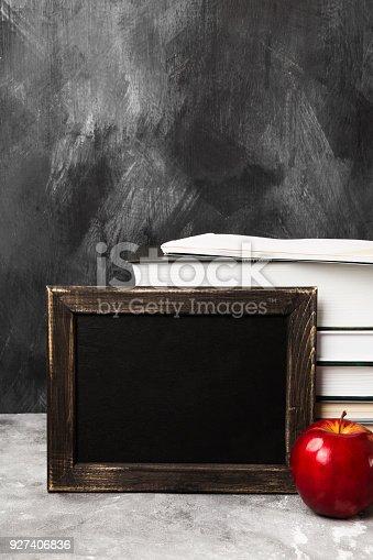 istock School attributes - black board, books, colored pencils, notebook, apple on dark background. Copy space 927406836
