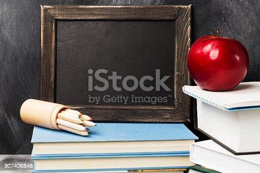 istock School attributes - black board, books, colored pencils, notebook, apple on dark background. Copy space 927406848