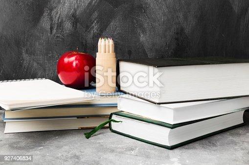istock School attributes - books, colored pencils, notebook, apple on dark background 927406834