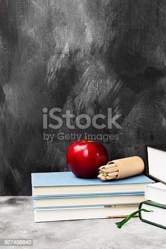 istock School attributes - books, colored pencils, notebook, apple on dark background 927406840