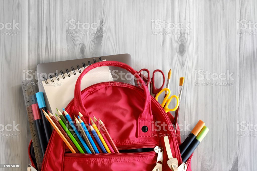 School backpack and school supplies on white wood table background. Back to school concept. stock photo
