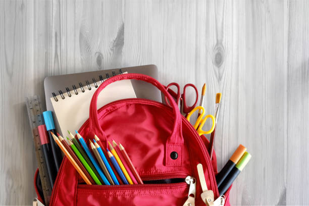 school backpack and school supplies on white wood table background. back to school concept. - school supplies stock pictures, royalty-free photos & images