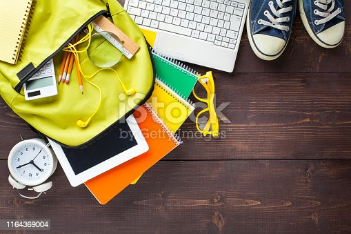 istock School backpack and school supplies on wooden background 1164369004