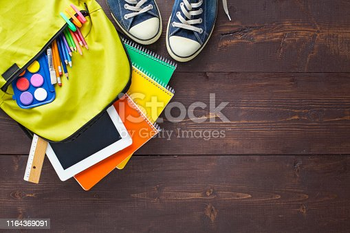 istock School backpack and school supplies on wooden background 1164369091