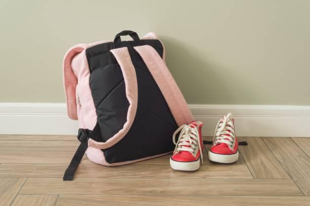 school backpack and sneakers on the floor in home interior - cartella scolastica foto e immagini stock